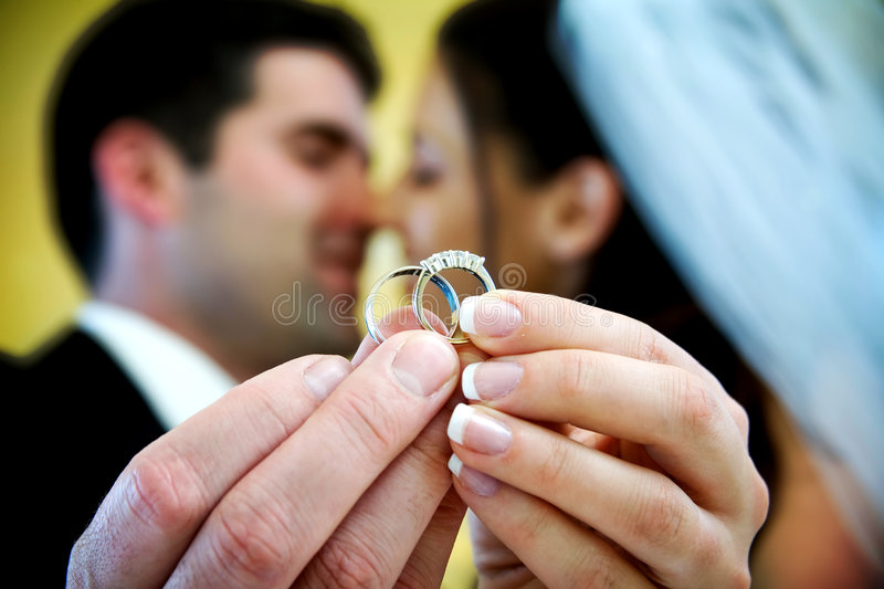 Wedding ring. The bride and groom are holding up the wedding rings and kissing in the background. NOTE: this photo has a very shallow depth of field stock image