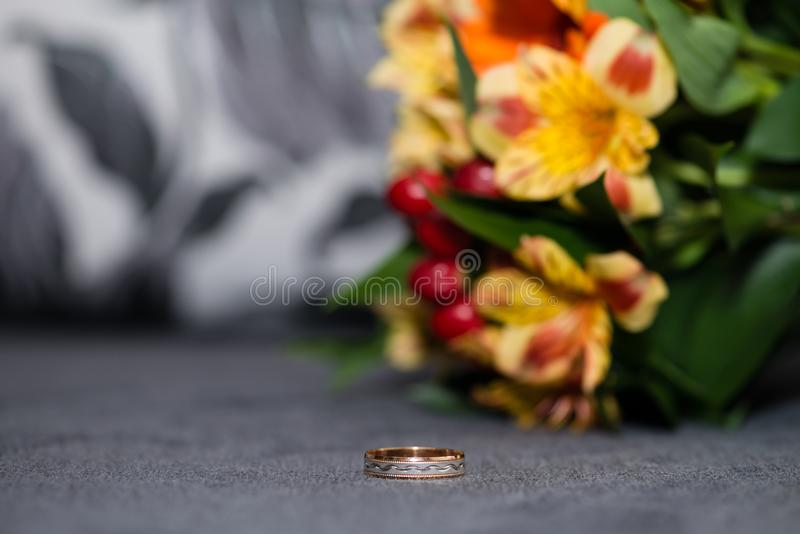 Wedding ring on the background of bride`s bouquet royalty free stock images