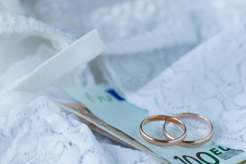 Wedding ring and banknotes on bridal lace dress background. Marriage of convenience stock photography