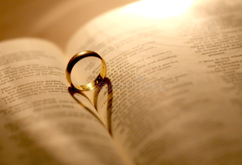 A wedding ring in the bible. With shadow of heart shape royalty free stock image