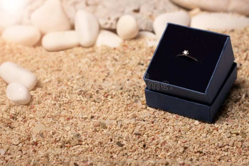 Wedding ring in a blue box. On the background of sand and stones royalty free stock image