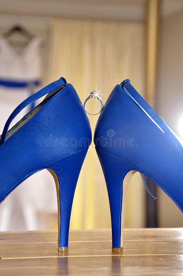 Wedding ring in between bridal shoes stock photography
