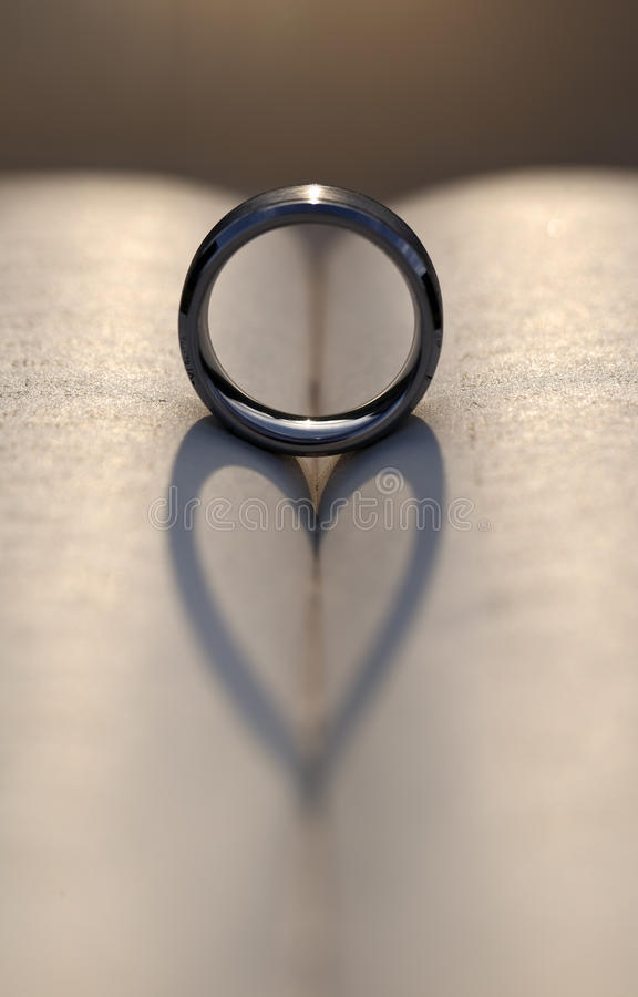 Wedding Ring Casting a Heart Shadow Between Pages of a Book royalty free stock image
