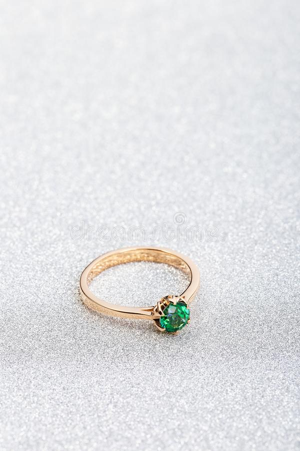 Wedding ring with emerald green gemstone on white sparkle background. Wedding ring with emerald green gemstone on white glossy background. Rose gold engagement royalty free stock image