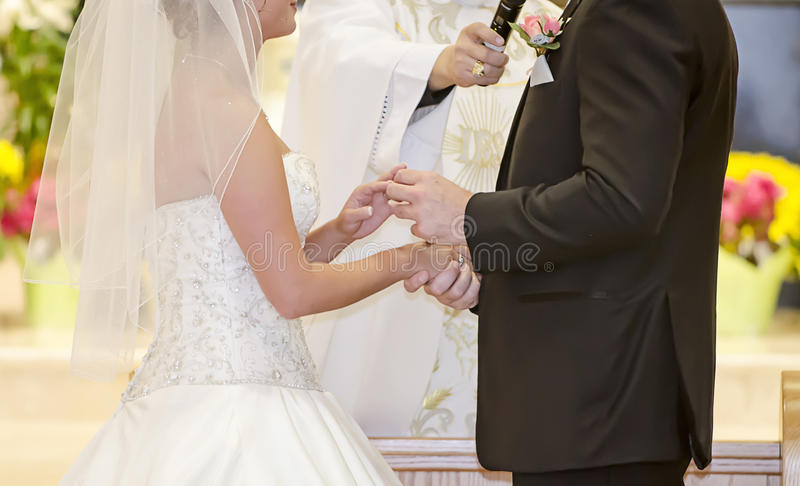 Wedding ring exchange. Close up of wedding ring exchange during ceremony stock photography