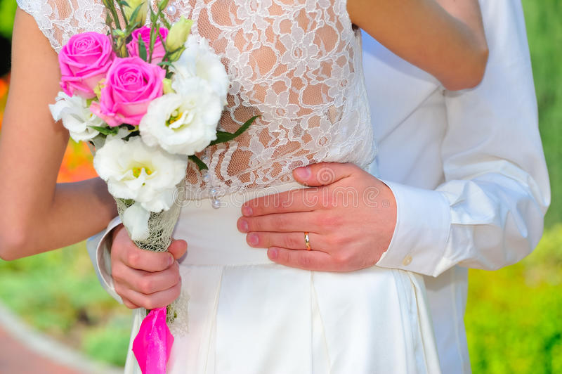 The wedding ring: groom hand embraces the waist of the bride. We. Dding bouqet. Close up stock image