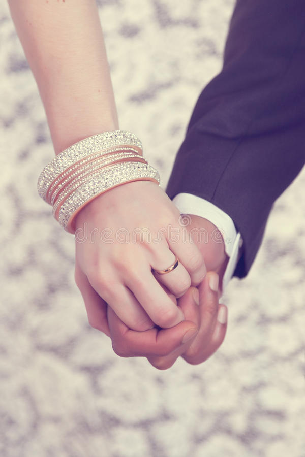 Wedding ring on hand. Male and female joined hands on wedding day stock photo