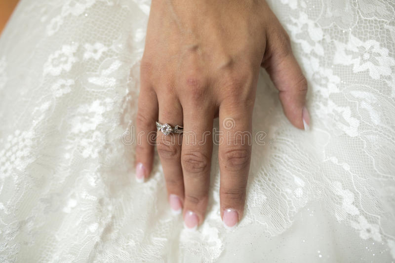 Wedding ring on hand. Wedding ring on the hand of a white dress royalty free stock photography
