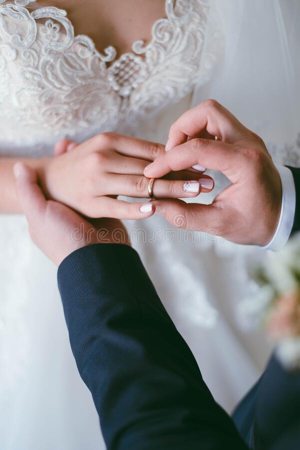 Free Wedding Ring On The Finger. The Groom Puts The Ring On The Bride. Wedding Stock Images - 212386784