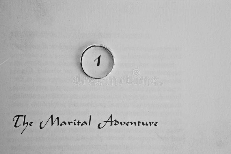 A wedding ring on a page that states the marital adventure. Circling the number one 1 stock photo