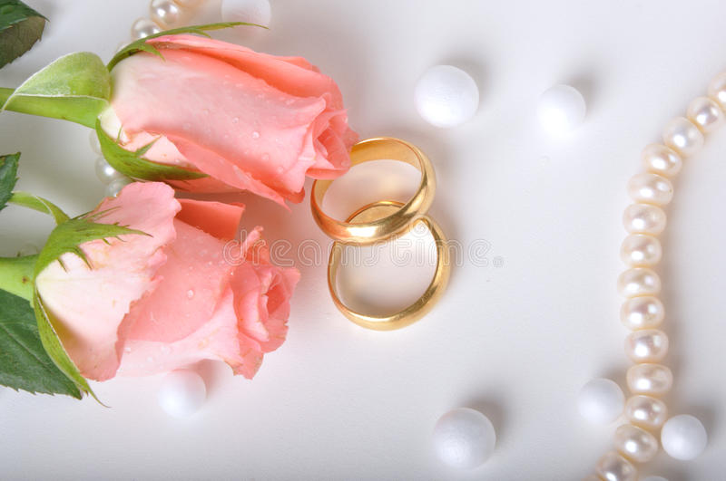 Wedding ring & rose. Pair of wedding rings with pink roses and pearls on white royalty free stock photo