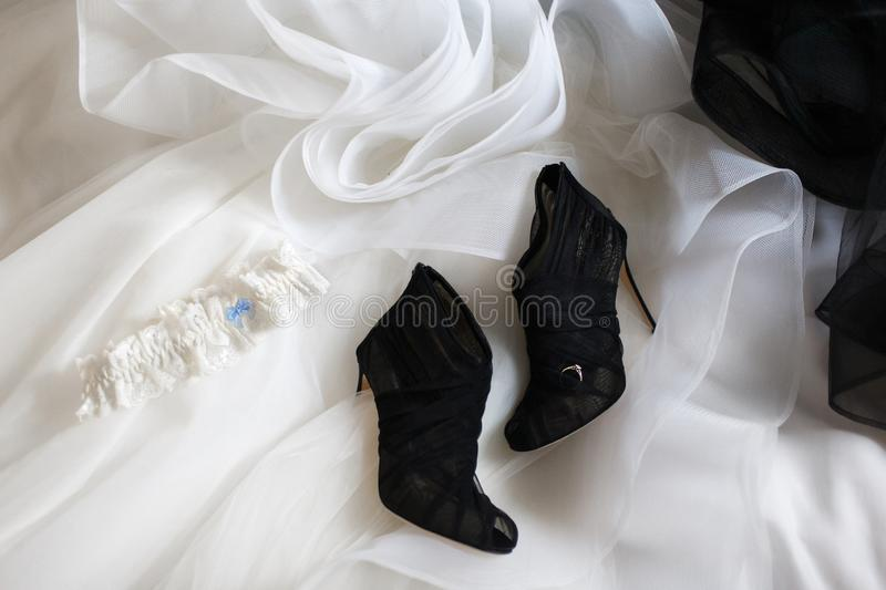 Wedding ring on the wedding shoes and wedding dress royalty free stock photography