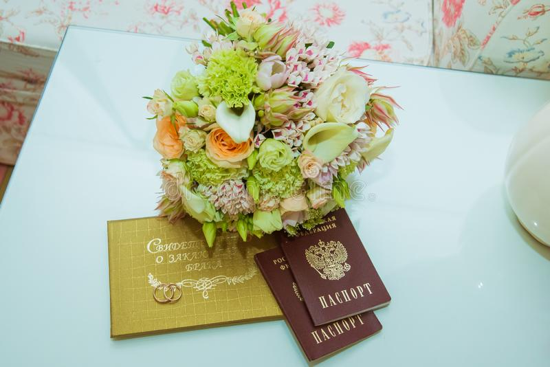 Wedding ring. Two gold rings with diamonds are in a red box, next to the bride`s bouquet, marriage certificate and passport of th stock photo