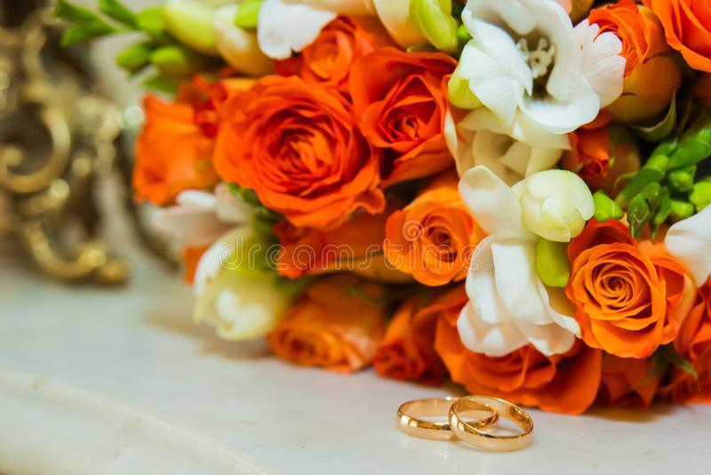 Wedding ring. Two gold vintage rings and a bride`s bouquet of orange roses and white flowers royalty free stock images