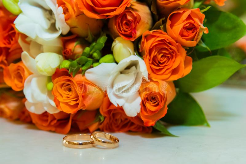 Wedding ring. Two gold vintage rings and a bride`s bouquet of orange roses and white flowers stock images