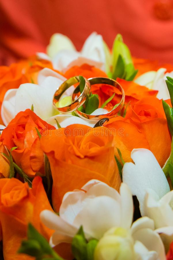 Wedding ring. Two gold vintage rings and a bride`s bouquet of orange roses and white flowers royalty free stock image