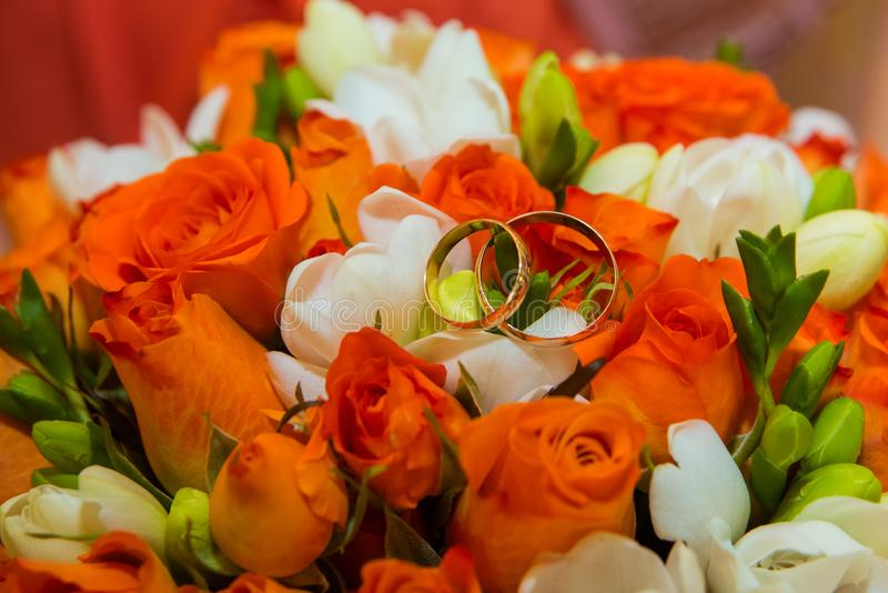 Wedding ring. Two gold vintage rings and a bride`s bouquet of orange roses and white flowers stock photography