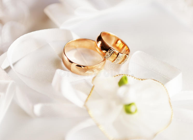 Wedding rings. On a satiny fabric with bow stock photography