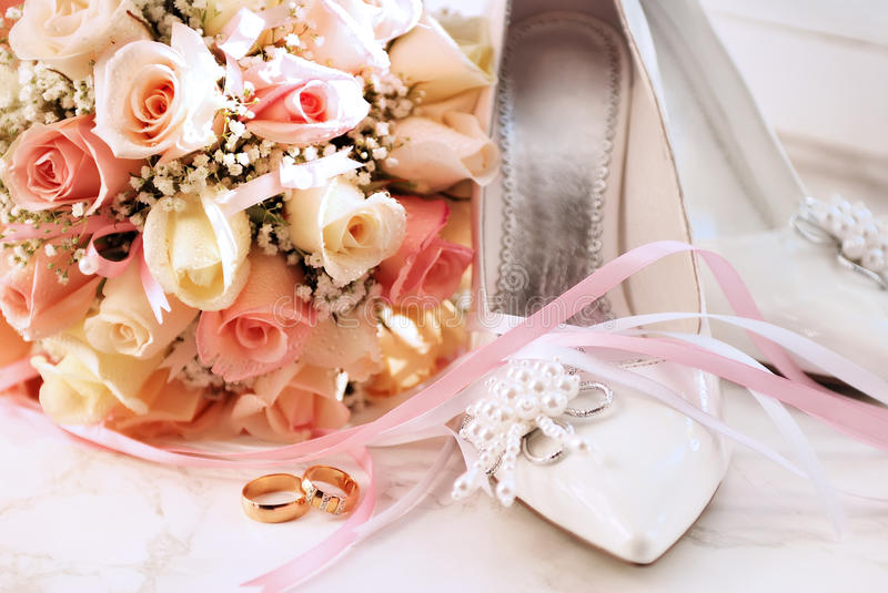 Wedding rings. Bouquet and bridge shoes stock photos
