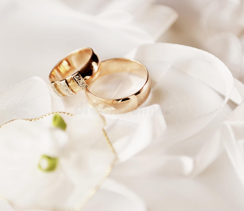 Wedding rings. On a satiny fabric with bow royalty free stock images