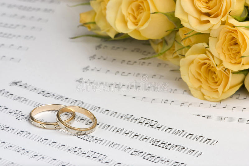 Wedding rings. And roses with musical sheet background stock photo