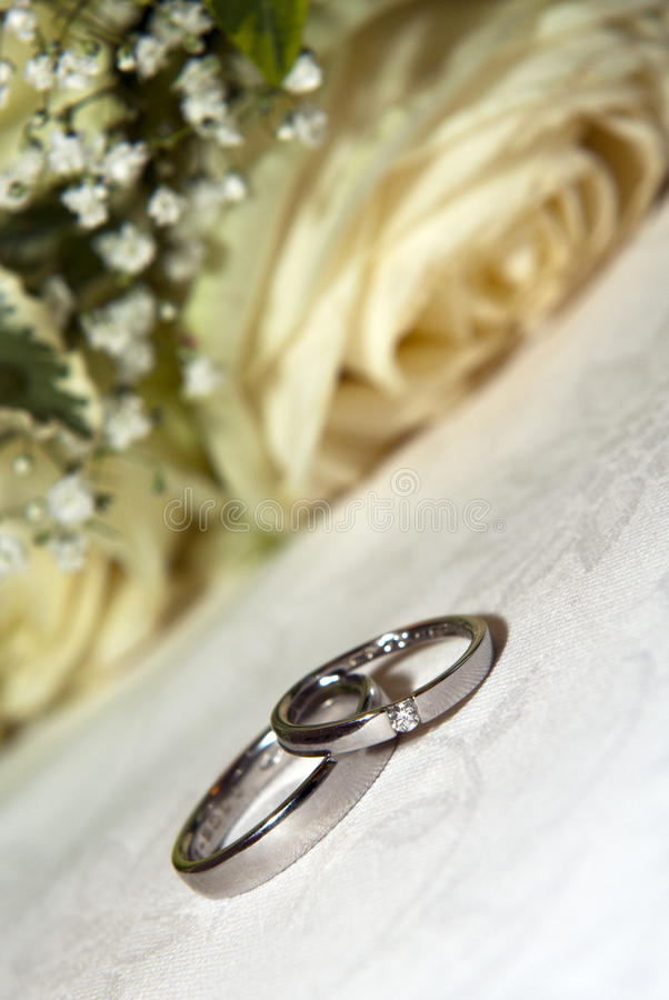 Wedding rings. And roses bouquet royalty free stock image