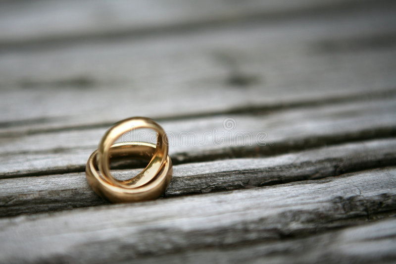 Wedding rings. Two wedding rings on top of each other lying on a piece of wood