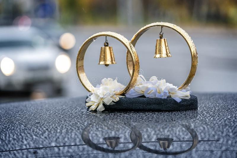Wedding rings with bells in drops of rain on the roof of the car royalty free stock photography