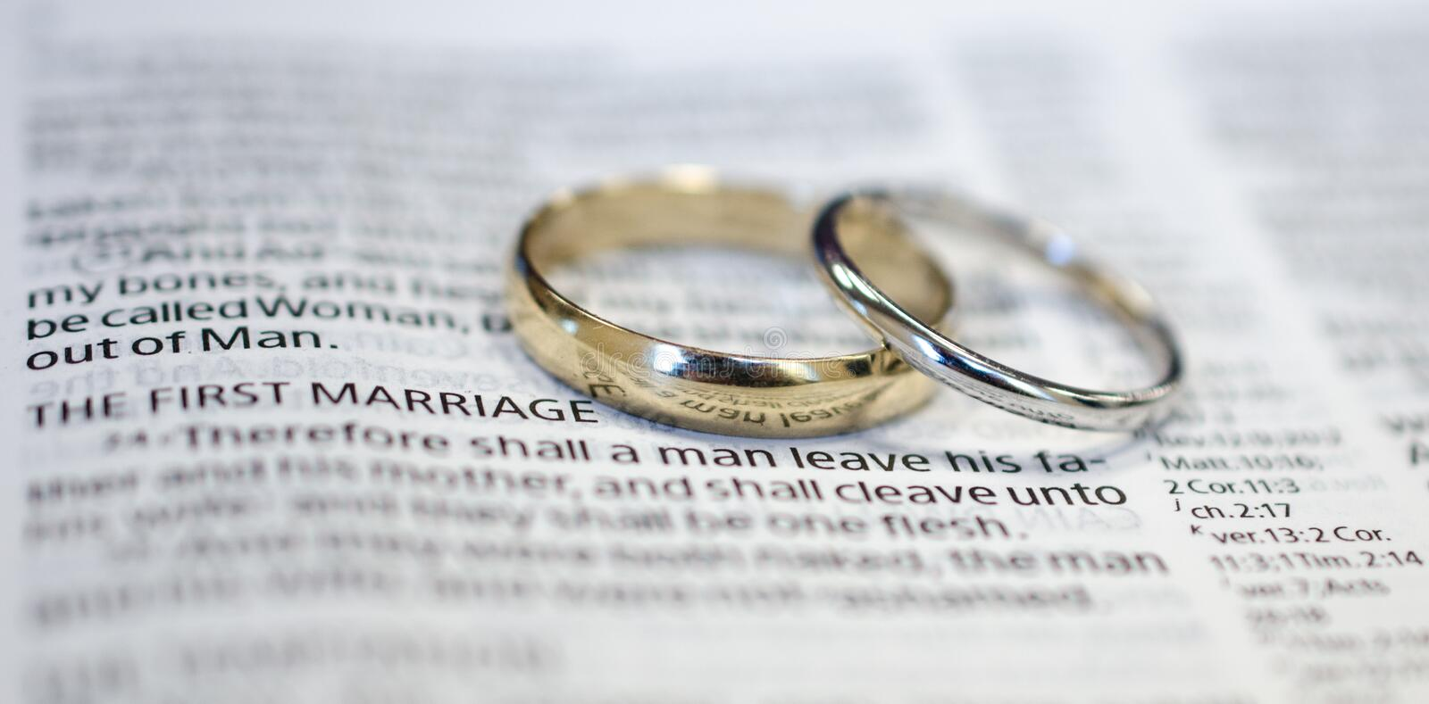Wedding rings on Bible scripture. White gold wedding bands on Bible scripture, The first marriage, Genesis 2:24 Therefore shall a man leave his father and his royalty free stock photo