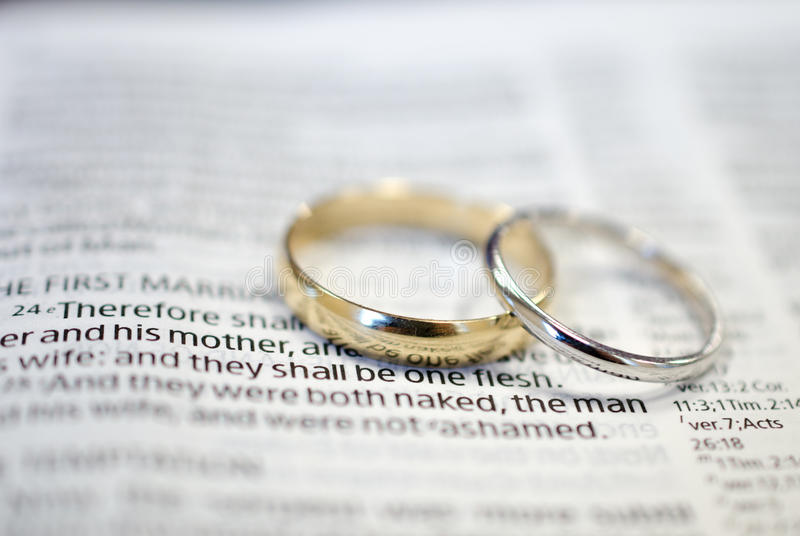 Wedding rings on Bible scripture. White gold wedding bands on Bible scripture, The first marriage, Genesis 2:24 Therefore shall a man leave his father and his stock photo
