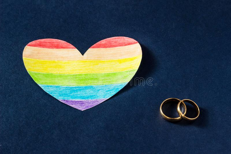 Wedding rings on a blue background and a heart in the form of a flag lgbt, same-sex marriage. Wedding rings on a blue background and a heart in the form of a royalty free stock photos