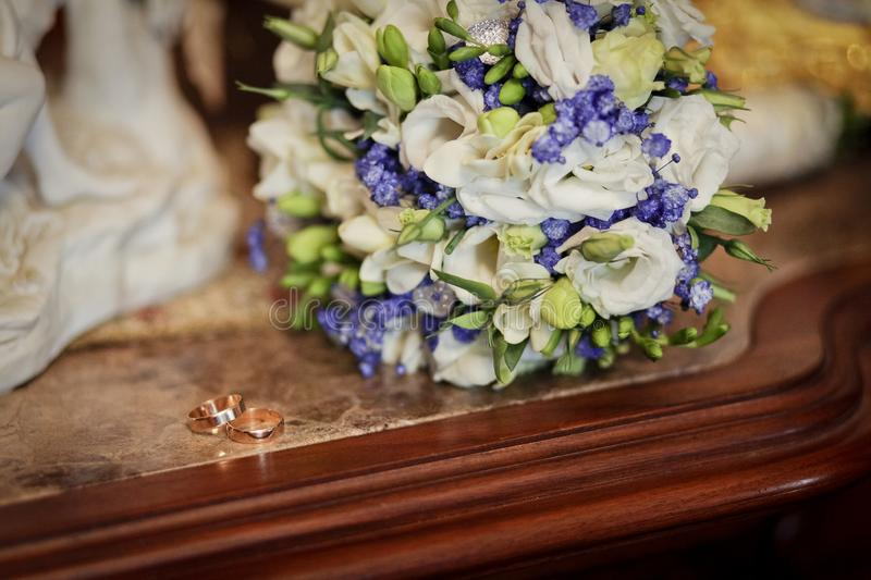 Wedding rings and blue and white wedding bouquet laying on the table in the vintage interior royalty free stock photography