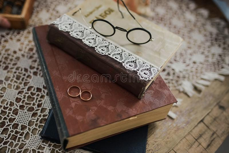 Wedding rings on the book. Wedding rings on a pile of books with glasses royalty free stock photography