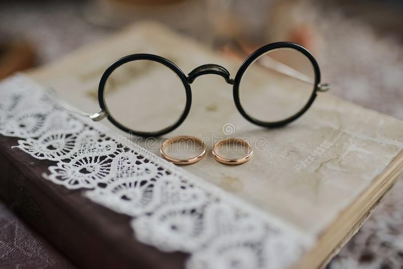 Wedding rings on the book. Wedding rings on a pile of books with glasses close royalty free stock image