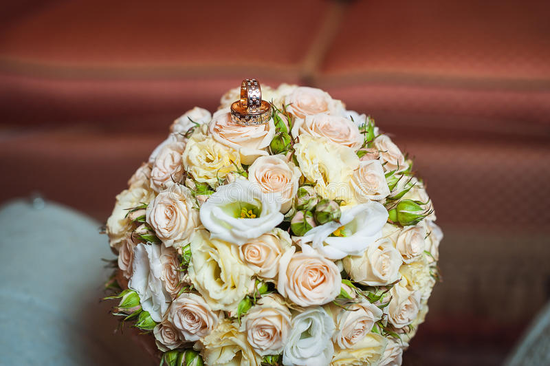 Wedding rings on a bouquet of cream roses.  royalty free stock photography