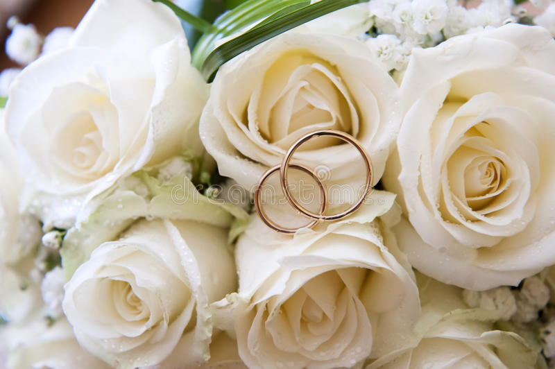 Wedding rings on a bouquet of roses. Wedding rings on a bouquet of white roses stock photos