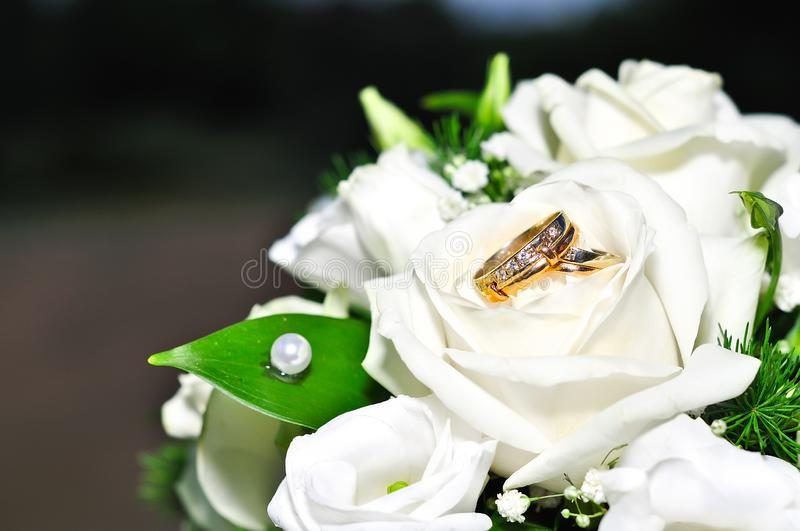 Wedding rings on a bouquet of white flowers royalty free stock photos