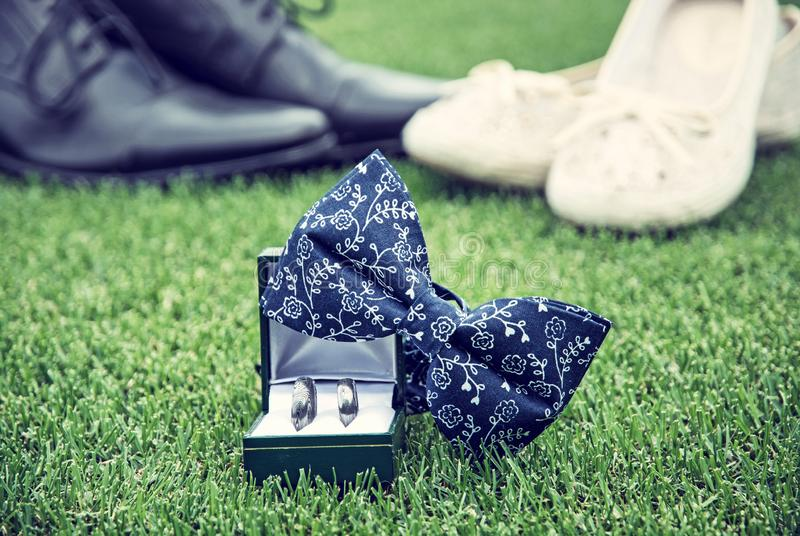 Wedding rings, bow tie and women`s and men`s shoes on grass. Wedding rings, bow tie and women`s and men`s shoes on the green grass. Symbol of love. Blue photo stock photography