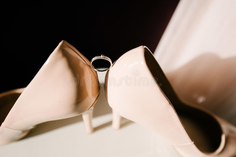Wedding rings of the bride and groom between the wedding shoes of the bride royalty free stock images