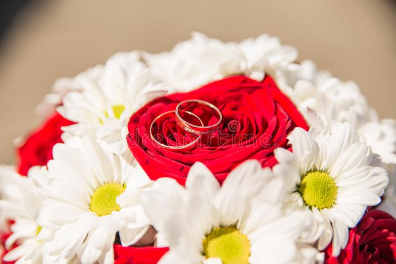 Wedding rings are on the bride`s bouquet. Wedding bouquet of white daisies and red roses. Wedding background for cards and stock photo