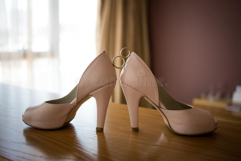 Wedding rings between bride`s pink shoes. Ceremony royalty free stock photos