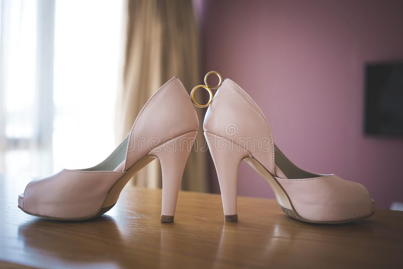 Wedding rings between bride`s pink shoes. Ceremony royalty free stock image
