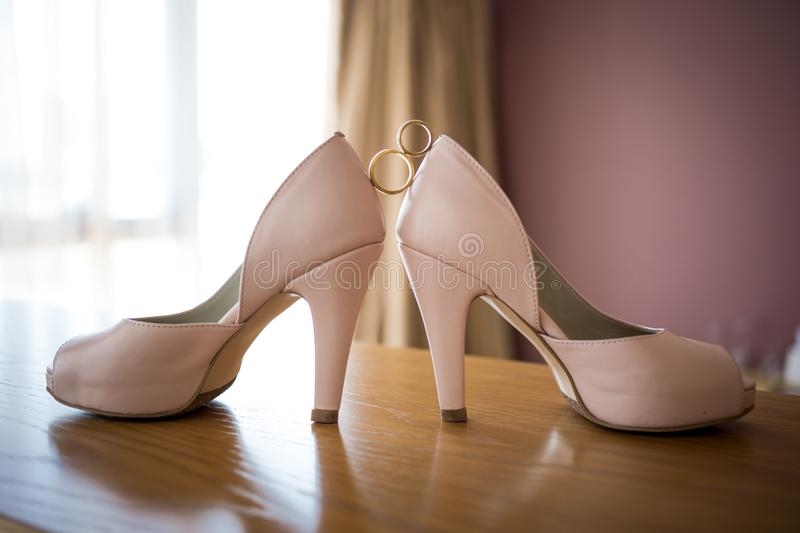 Wedding rings between bride`s pink shoes. Ceremony stock image