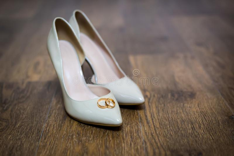 Wedding rings on the bride`s shoes. Wedding. Decor. Bride`s shoes. Wedding bride`s shoes and rings. Wedding white shoes stock photography