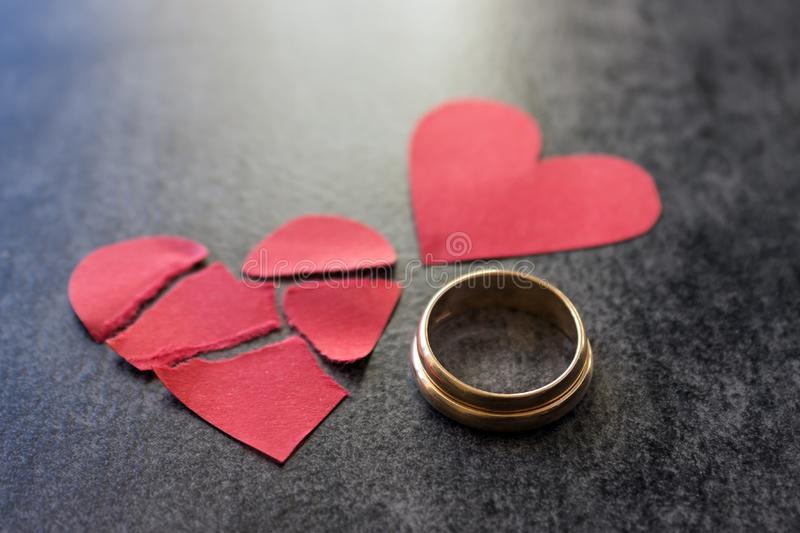 Wedding rings and broken red heart. Black background. The conce. Wedding rings and broken red heart. The concept of divorce, parting, infidelity .Selective focus royalty free stock photos