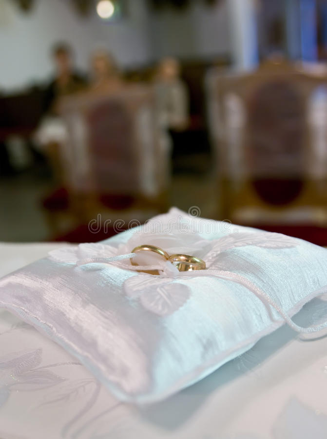 Wedding rings in church. Golden wedding rings on a cushion in a church royalty free stock images