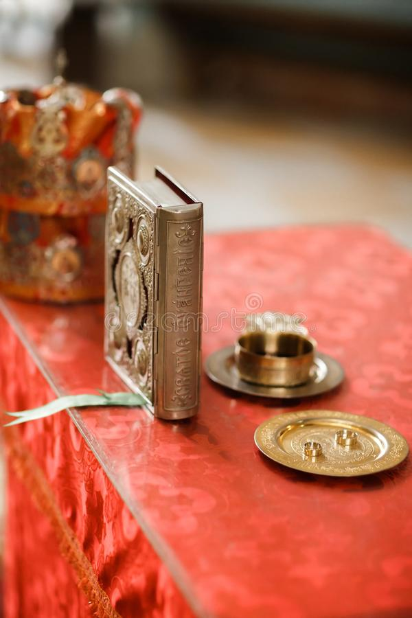 Wedding rings, crowns and bible at the table with cross and glass of vine stock images