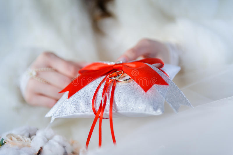 Wedding rings on decorative white pillow. Golden wedding rings on red, crimson and white ring pillow with red crimson bow and ribbons in hands of bride royalty free stock photography