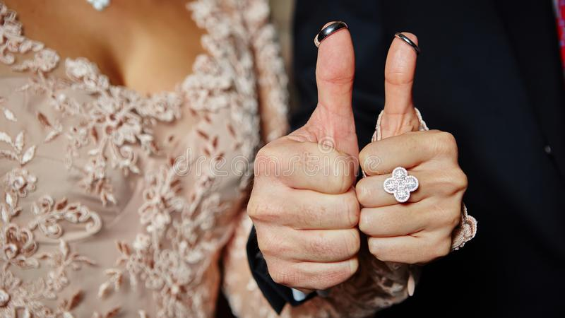 Wedding rings on fingers painted with the bride and groom stock images