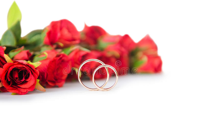 The wedding rings and flowers isolated on white background. Wedding rings and flowers isolated on white background royalty free stock photos